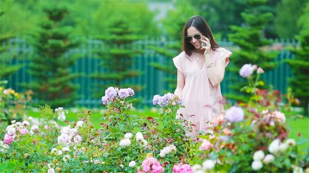 closed : Young girl in a flower garden among beautiful roses. Smell of roses