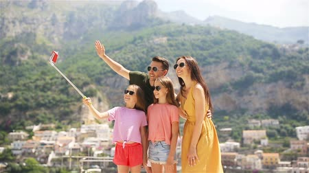 amalfitana : Parents and kids taking selfie photo background Positano town in Itali on Amalfi coast