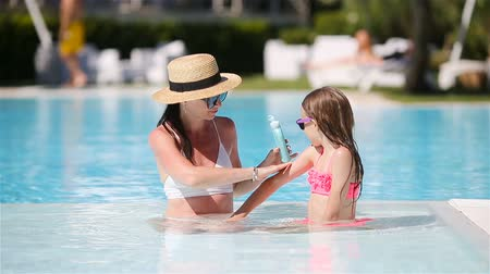 ultraviolet : Young mother applying sun cream to daughter nose