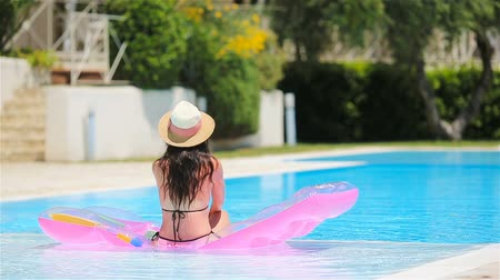 inflável : Young woman in bikini air mattress in the big swimming pool