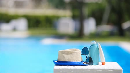 koruma : Suncream, hat, sunglasses near swimming pool