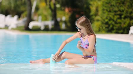 koruma : Little girl with sunscreen in the swimming pool