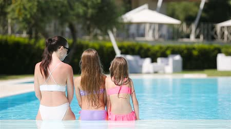 pływanie : Mother and two kids enjoying summer vacation in luxury swimming pool