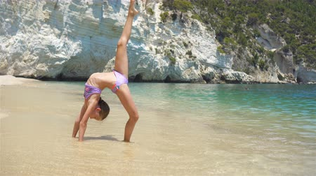 gymnasta : Active little girl at beach having a lot of fun. Cute kid making sporty exercises on the seashore Dostupné videozáznamy