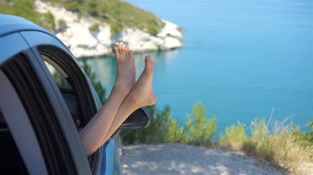 bare foot : Close up of little girl feet showing from car window background sea Stock Footage