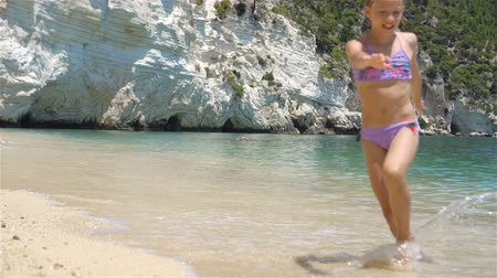 kind : Active little girl at beach having a lot of fun. Cute kid making sporty exercises on the seashore Stockvideo