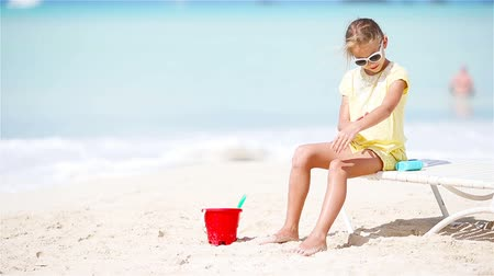 koruma : Little girl with bottle of sun cream sitting at tropical beach Stok Video