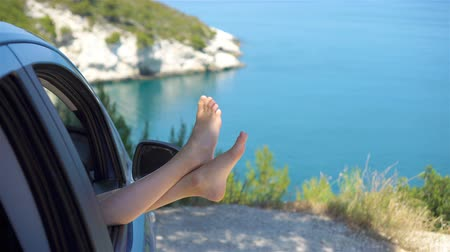 Close up of little girl feet showing from car window background sea Wideo