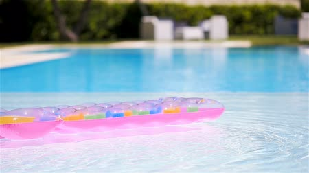 Pink inflatable mattress floating on water surface in swimming pool