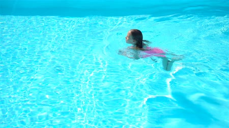 Adorable little girl swimming at outdoor swimming pool Wideo