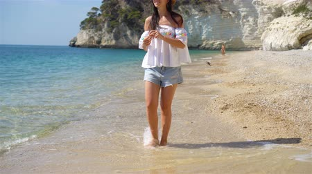 Young beautiful woman on white sand tropical beach. Caucasian girl in hat background the sea Wideo