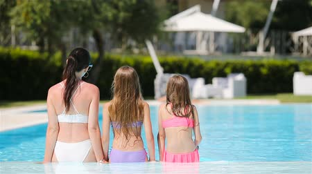 солнечные ванны : Mother and two kids enjoying summer vacation in luxury swimming pool