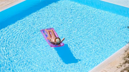 zonnebank : Young woman in bikini air mattress in the big swimming pool