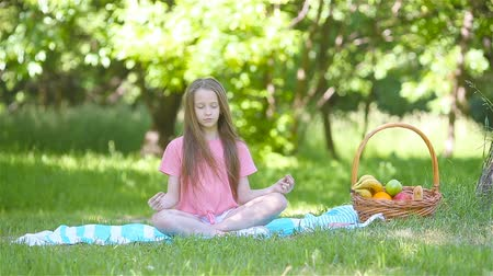 Little girl in yoga position in the park. 動画素材