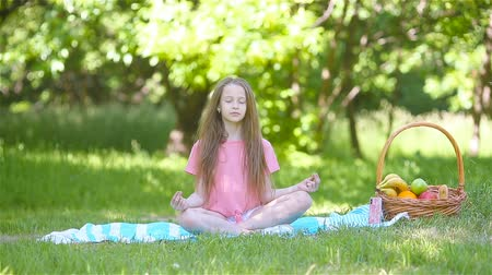 Little girl in yoga position in the park. Wideo
