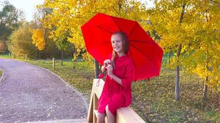 Happy child girl laughs under red umbrella Wideo