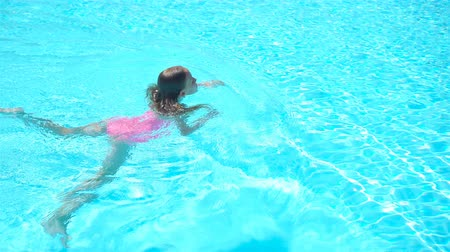 Adorable little girl swimming at outdoor swimming pool 動画素材