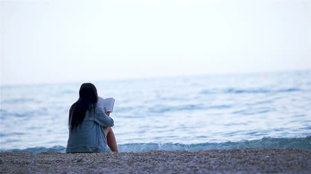 Young woman reading on tropical white beach