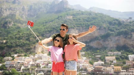 amalfitana : Father and kids taking selfie photo background Positano town in Itali on Amalfi coast