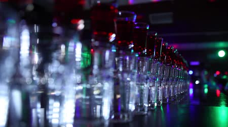 trabalho : Variety of colorful green blue yellow red and white beautiful alcohol sweet shooters shots cocktail fresh beverage in small glasses standing in row on bar studio closeup, Vídeos