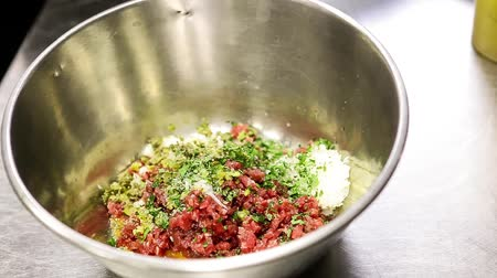 capers : mixing steak tartare ingredients in a bowl Stock Footage