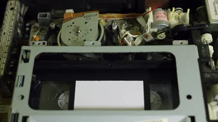 videocassette : VHS cassette is inserted into the player and pressed play Stock Footage