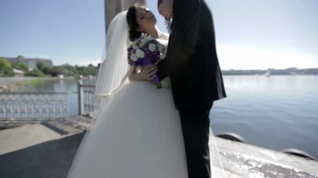 gracefully : groom kisses the bride against the backdrop of the lake