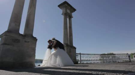 kolumny : groom kisses the bride against the backdrop of the lake