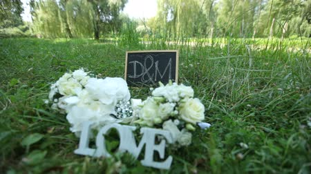 sziám : Wedding decoration word love , flowers and wooden plaque with the letters D and M on a background of green grass in the park