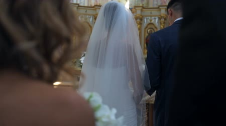 véu : bride and groom stand in the church on the background of a beautiful iconostasis. Back view of the crowd