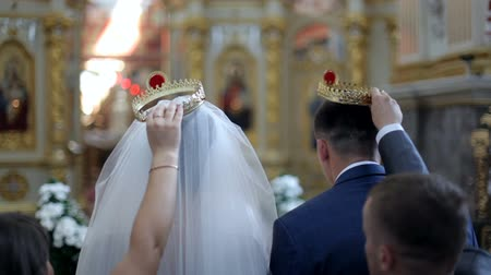 věčnost : bride and groom stand in the church on the background of a beautiful iconostasis. Sacrament of the wedding