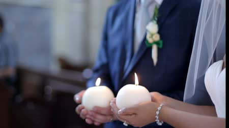 slaaf : bride and groom hold candles at the altar Stockvideo