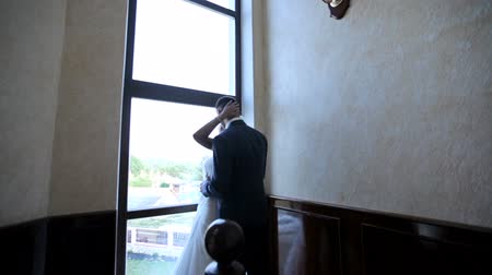 impatience : bride and groom kiss in the hotel lobby near the big window