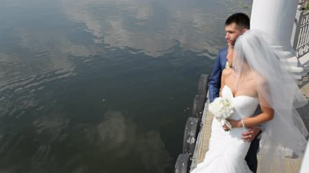 kolumny : Beautiful bride and groom are standing background of the lake. Happy newlyweds are standing at the pier.