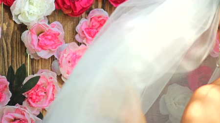 kaşları : Portrait of a happy bride. A beautiful bride in a veil is holding a bouquet of flowers against the background of a wooden wall with peonies.