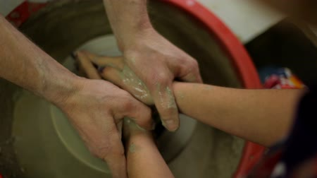 louça de barro : master corrects the pupils hands on the potters wheel while making a clay jug.