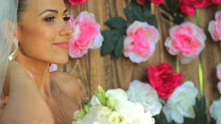 kaşları : Portrait of a happy bride. beautiful bride in veil with a bouquet in hands against the background of a wooden wall with peonies.