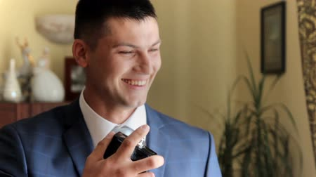 dezodorant : handsome man in the apartment uses cologne. wedding day Wideo