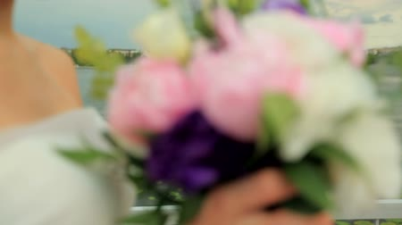 piwonie : Beautiful bride with a wedding bouquet on a blue lake background Wideo