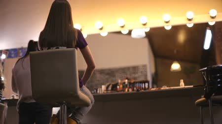 make photo : girl is sitting in the salon of the make-up artist and she is doing fashionable make-up. Stock Footage