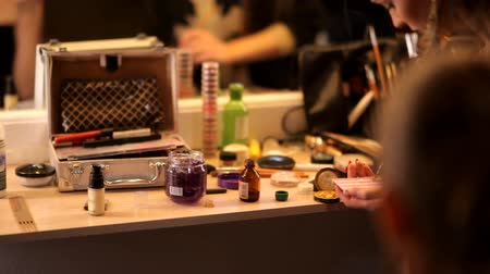 változatos : Professional cosmetics makeup on the table in the studio. Multicolored lipstick, shadows, a basis in a make-up.