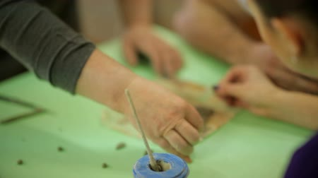 terrakotta : Master with students makes souvenirs from clay. Work process in an art workshop, work with clay.