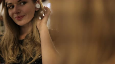 šik : Portrait of beautiful woman with wireless earphones. Pretty girl looking in the mirror and smiling. close-up
