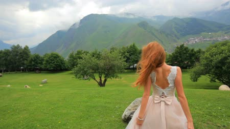 fiancee : Gorgeous bride blonde posing while looking at mountains. Attractive girl on a background of mountain scenery. Wedding day Stock Footage
