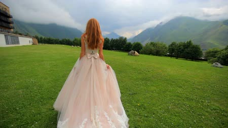 słoneczko : red-haired bride in a lavish dress walks along the green grass against the backdrop of the high mountains. Wedding day