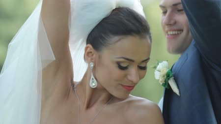 ulita : Happy bride and groom dancing in the park. Croissant newlyweds have fun in the park. Wedding day.