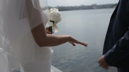 gracefully : bride and groom hold hands on a blue lake background.