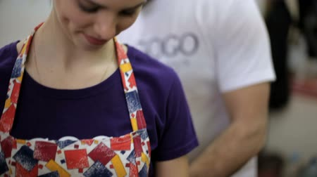 louça de barro : girl dresses an apron to work with clay in an art workshop