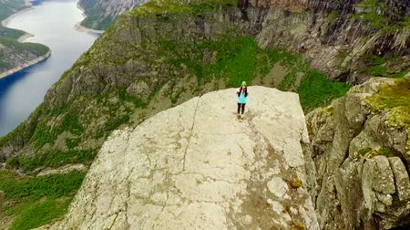 Скандинавия : Norway. girl is standing on the edge of the Trolltunga Стоковые видеозаписи