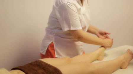 massager : girl enjoys a massage in the spa. Ayurvedic healing massage in six hands.